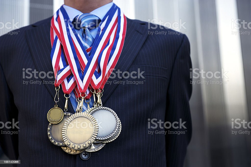 Businessman Standing Outdoors Decorated with Medals stock photo
