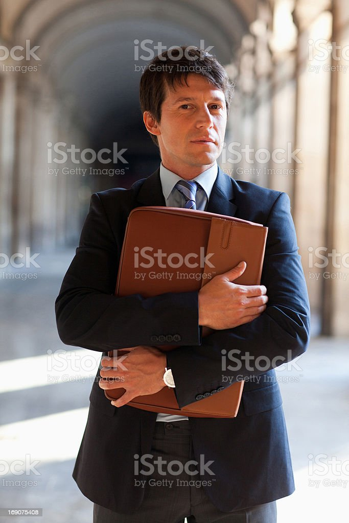 Businessman standing outdoors holding briefcase royalty-free stock photo
