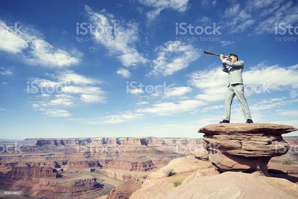 Businessman Standing Outdoors on Mesa Landscape with Telescope stock photo