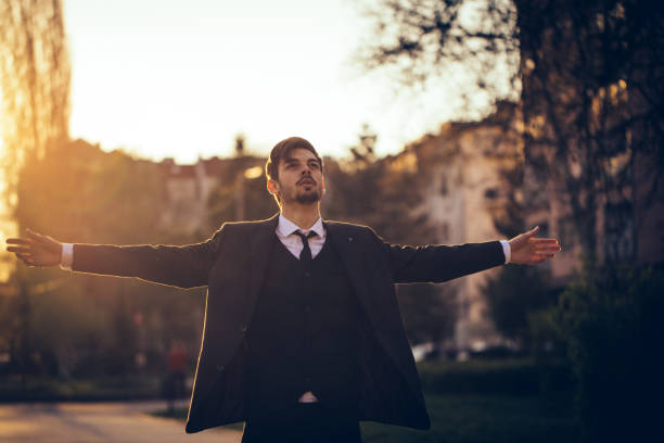 businessman standing outdoors with arms outstretched - arms outstretched stock photos and pictures