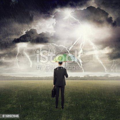 858837068 istock photo Businessman standing under an umbrella in field 616892846