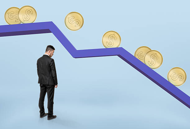 Businessman standing under falling graph with golden coins rolling down Businessman with his head bowed standing under falling graph with golden coins rolling down. Stock market selloff. Financial market. Economic crisis. depreciation stock pictures, royalty-free photos & images