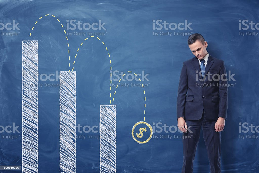 Businessman standing upset and column diagram with a dollar sign - foto de stock