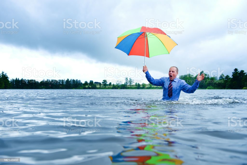Businessman standing waist up in water with a umbrella royalty-free stock photo