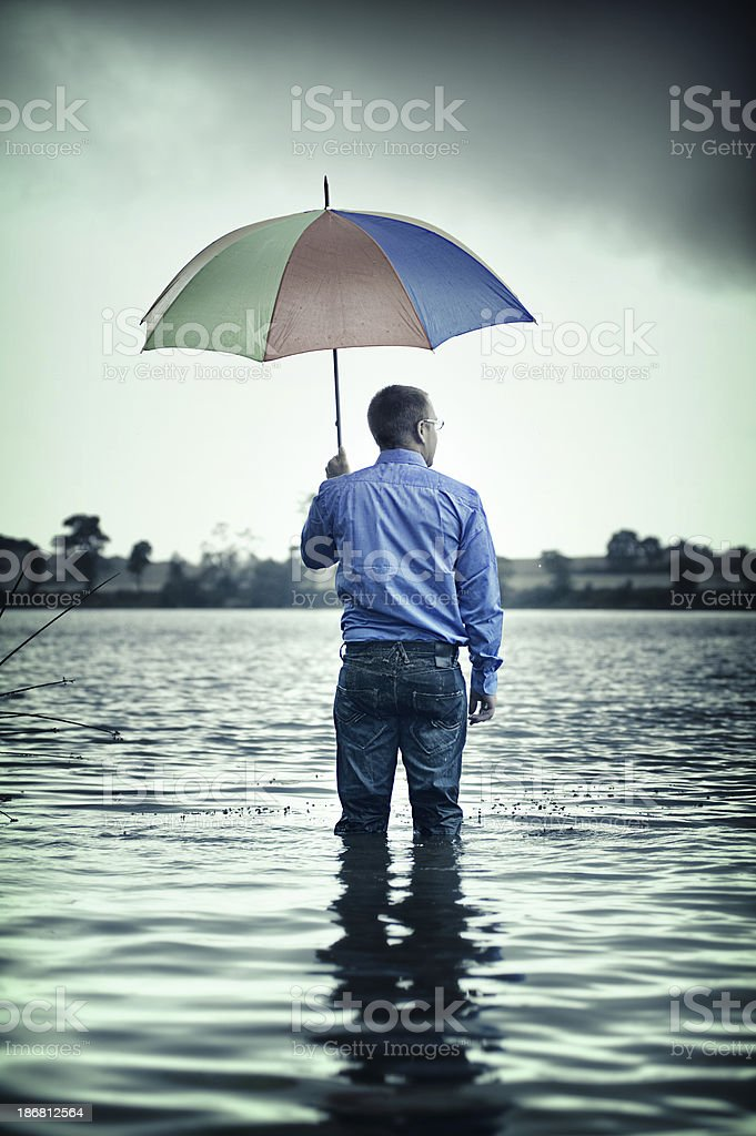 Businessman standing waist up in water with a umbrella stock photo