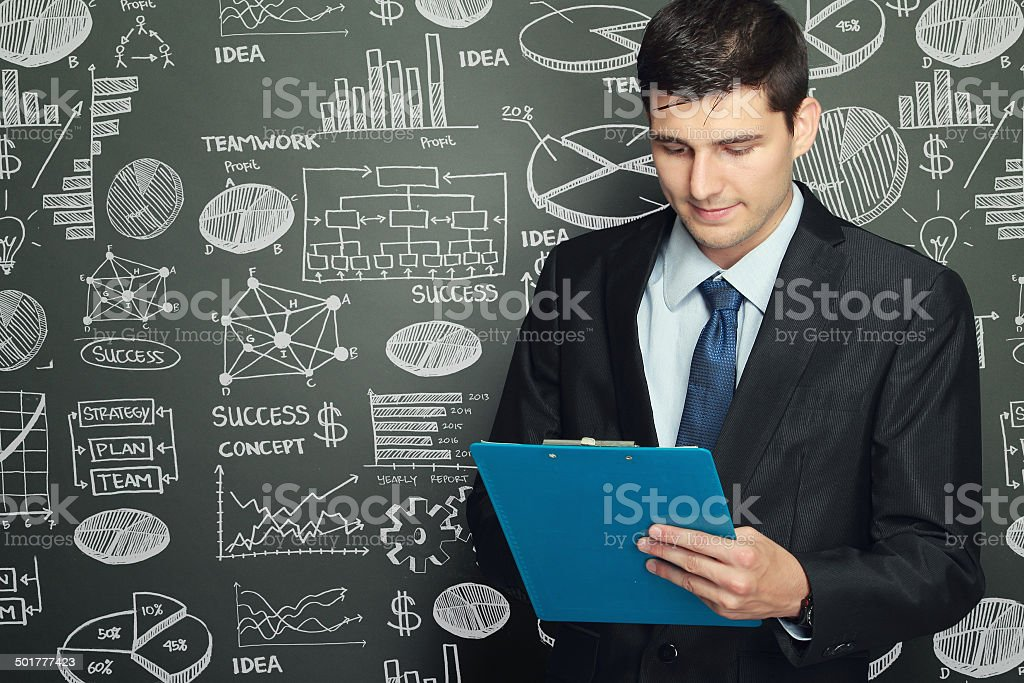 businessman standing while reading report stock photo