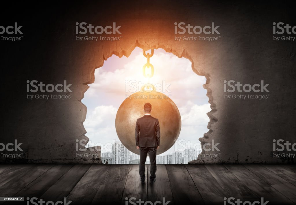 A businessman standing with a turned back and looking into the city through a wall hole made by a giant wrecking ball stock photo
