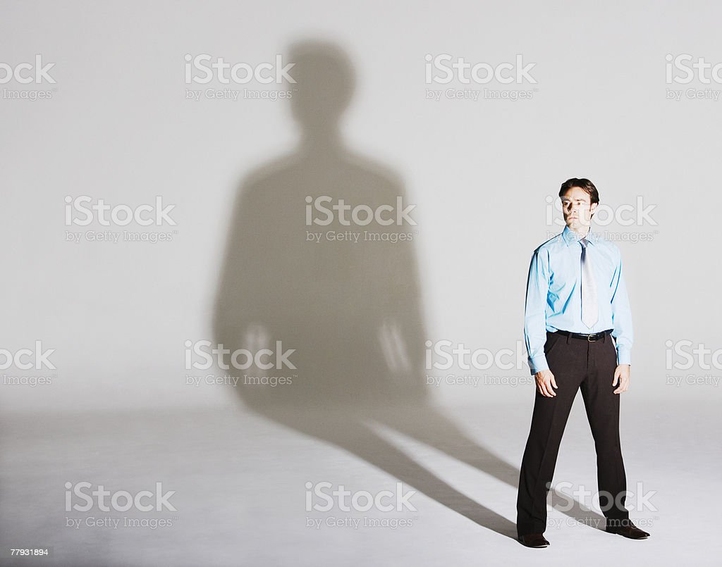 Businessman standing with arms by sides stock photo