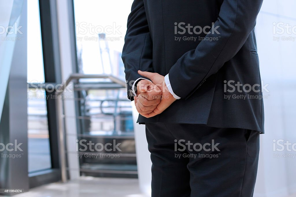 Businessman  standing  with both hands behind his back stock photo