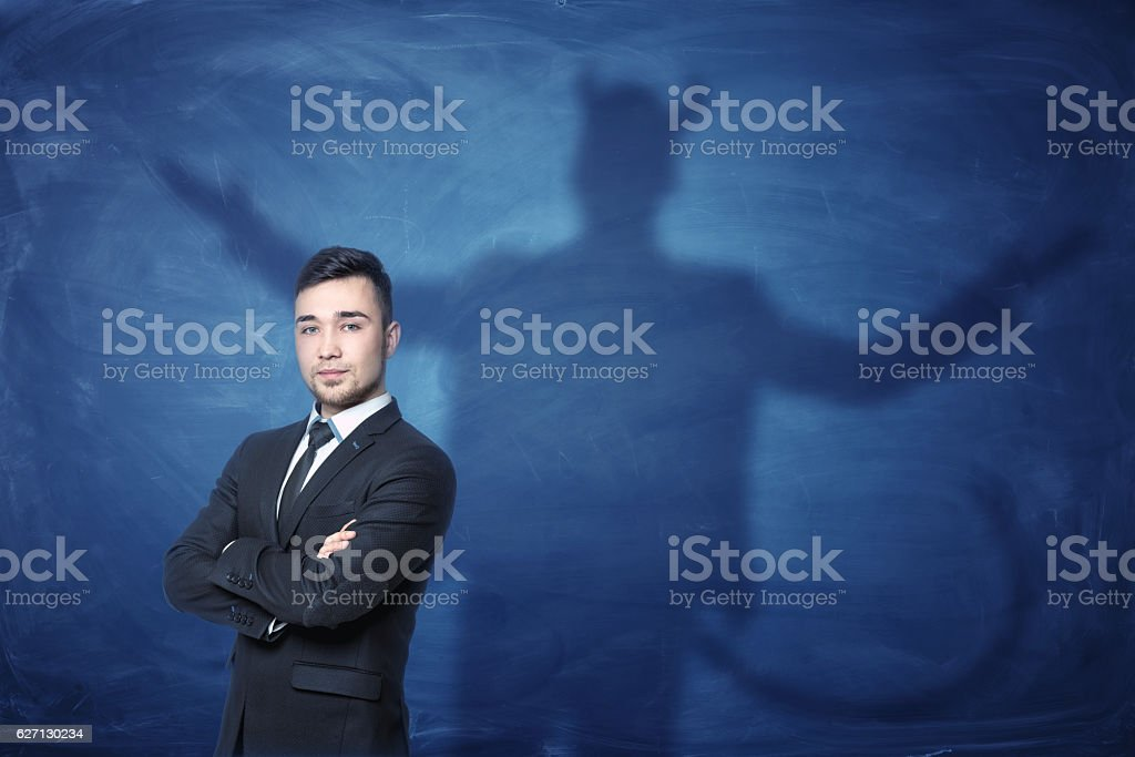 Businessman standing with hands across and his shadow on blue - 로열티 프리 경영자 스톡 사진