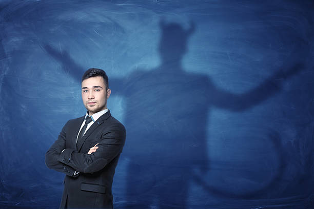 businessman standing with hands across and his shadow on blue - 악한 뉴스 사진 이미지
