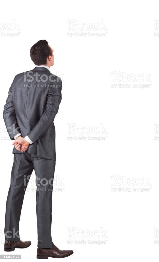 Businessman standing with hands behind back stock photo