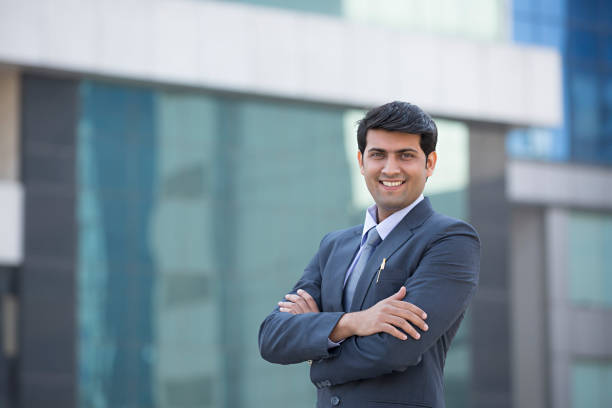 businessman standing with his arms folded - stock image - india stock pictures, royalty-free photos & images