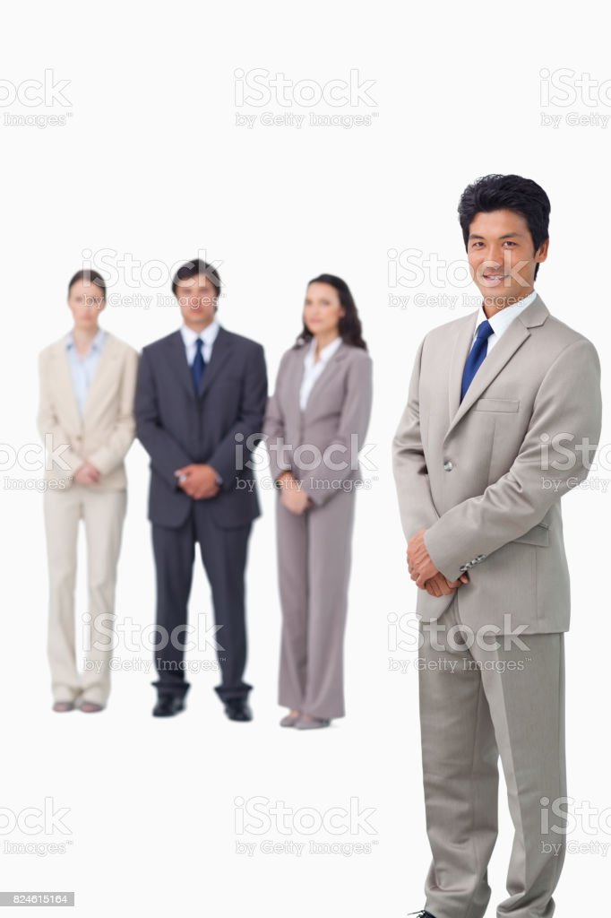 Businessman standing with his associates behind him stock photo