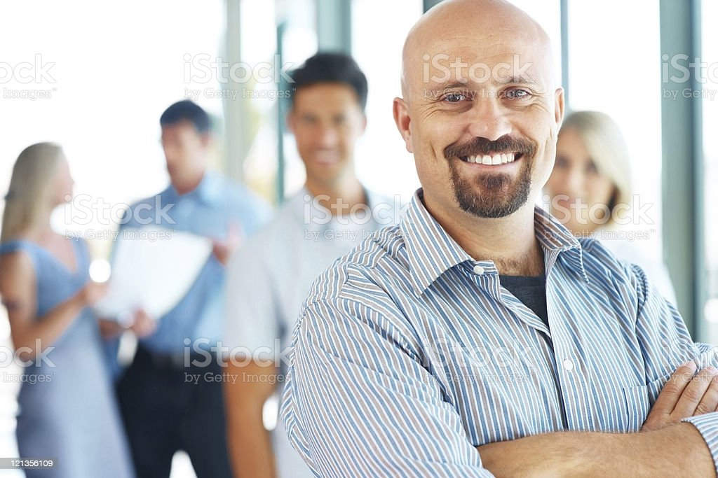 Businessman standing with his elite business team in the background royalty-free stock photo