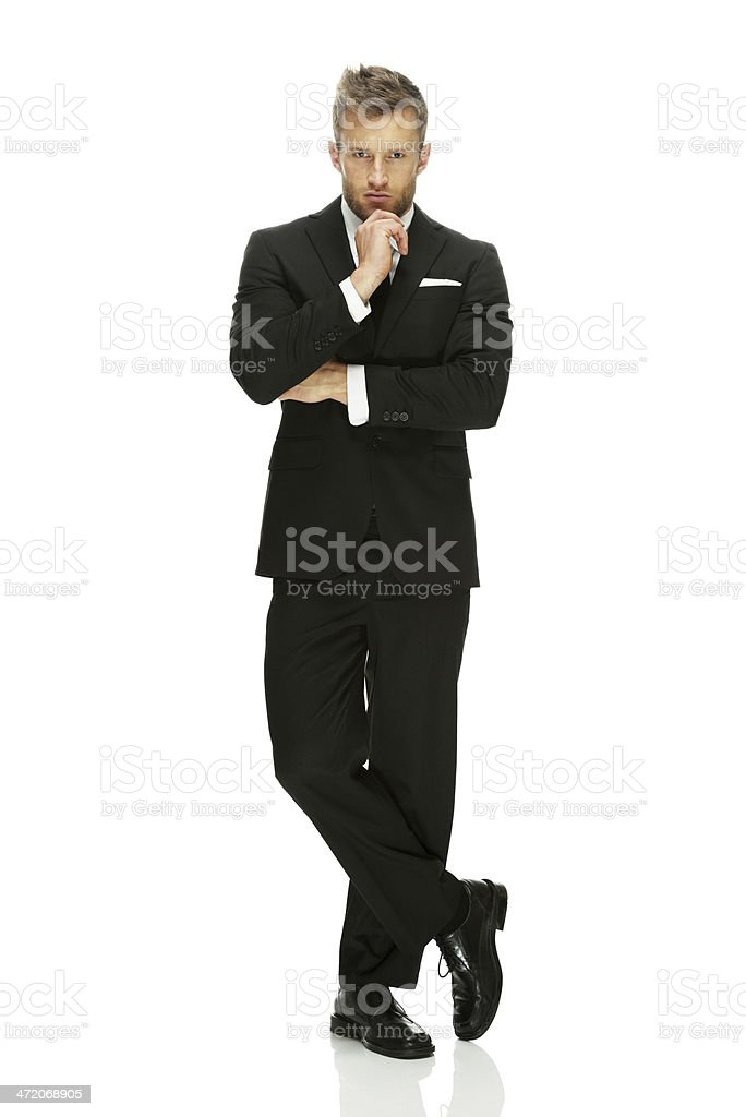 Businessman standing with his legs crossed stock photo