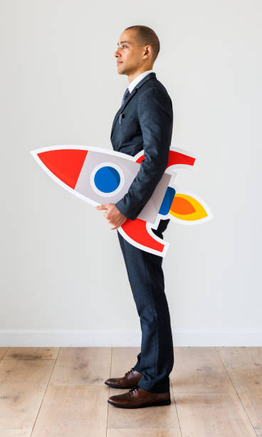 businessman standing with icons - rocket logo stock photos and pictures