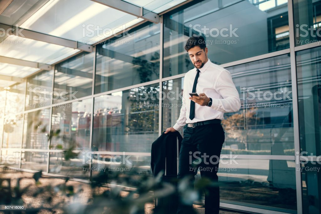 Businessman standing with luggage and using smart phone stock photo