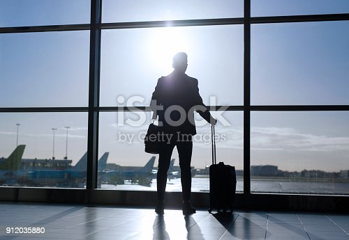 istock Businessman standing with suitcase in airport 912035880