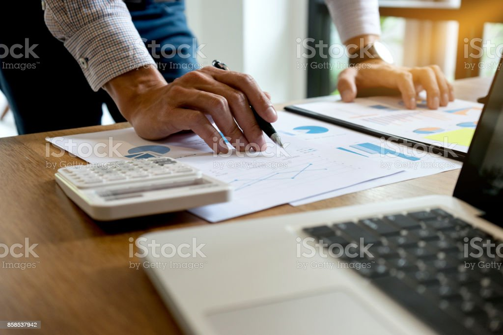 Businessman standing work on wood table prepare and read graph and paper stock photo