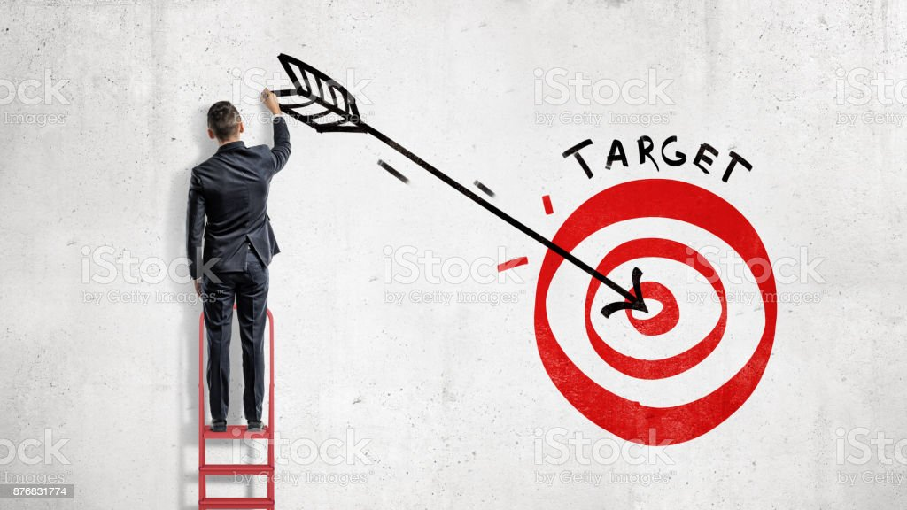 A businessman stands and draws on the wall a big arrow in the center of a red archery target. stock photo