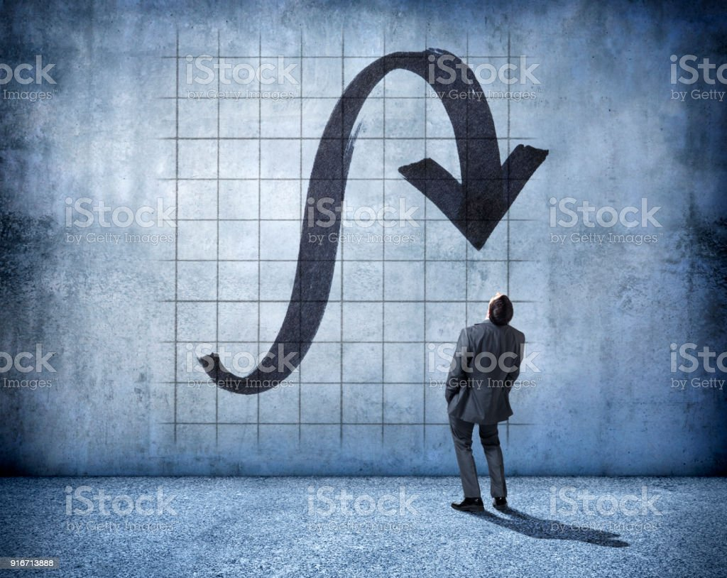 Businessman Stands And Looks Up At A Falling Arrow stock photo