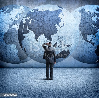 A rear view of a businessman as he stands and looks up at three interlocking globes on the wall in front of him as he tries to sort out the mess of geopolitical events. A globe rotated to Asia is in the center. Map source material courtesy of https://images.nasa.gov/