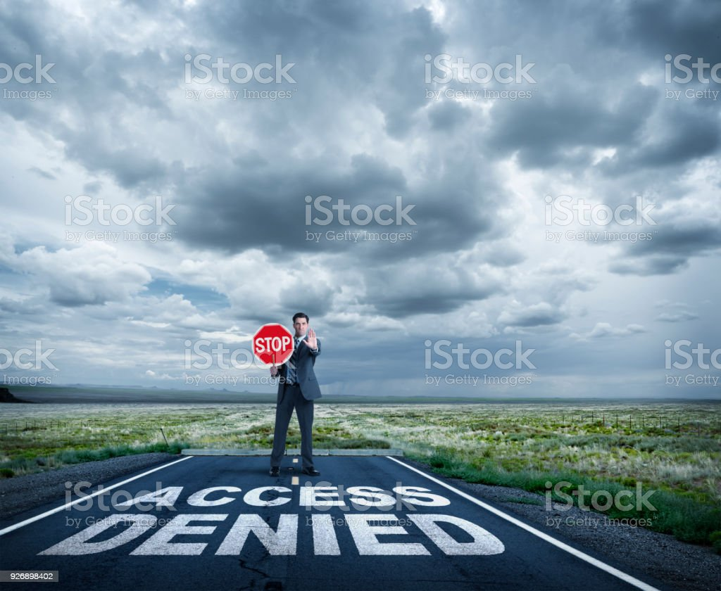 Businessman Stands At End Of Road Holding Stop Sign stock photo