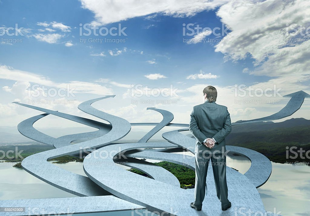 Businessman stands choosing his way stock photo