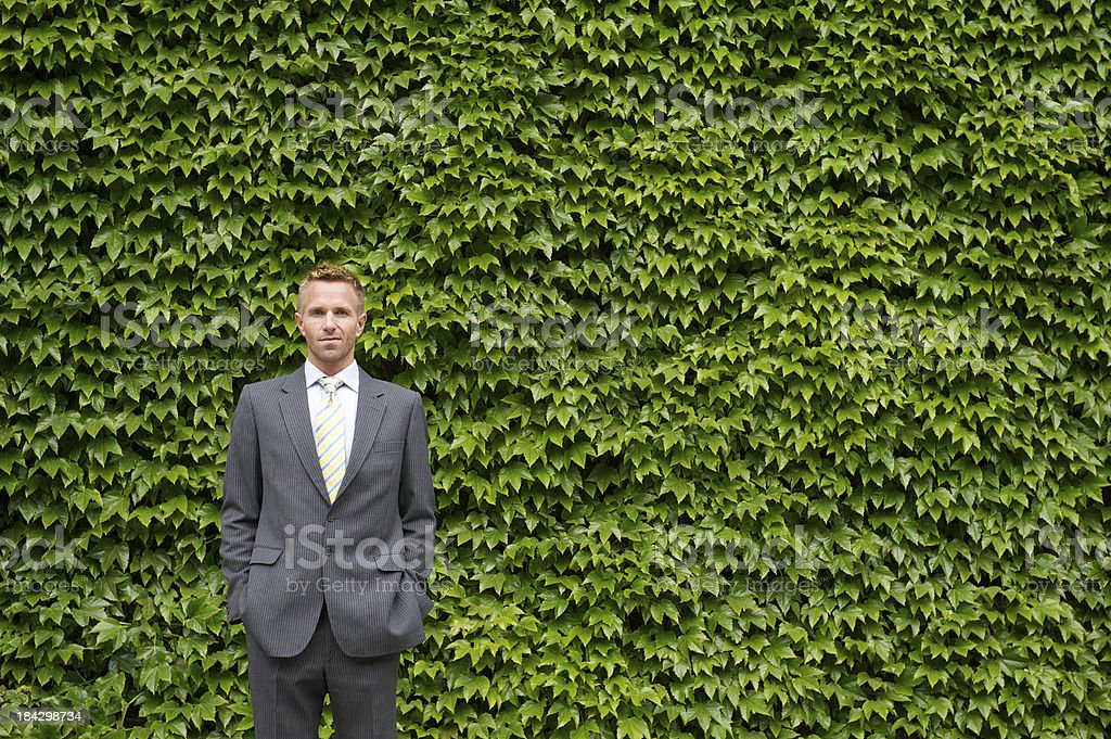 Businessman Stands in front of Green Ivy Wall royalty-free stock photo