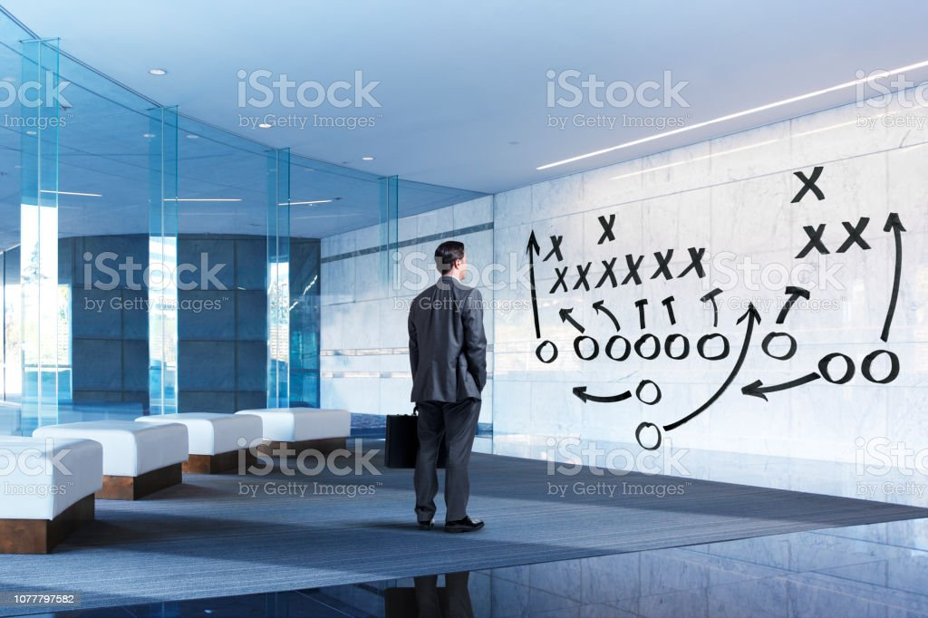Businessman Stands In Lobby Looking At Strategy Plan stock photo