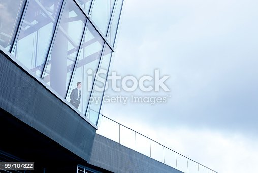 A businessman stands with his hands in his pockets inside a large office building and looks through the window into the distance. The overcast sky provides ample room for copy and text.