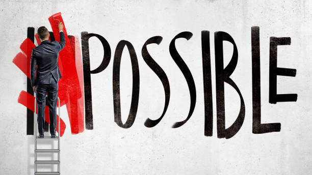 a businessman stands on a stepladder and hides the word impossible written on the wall using a red paint roller. - possible stock photos and pictures