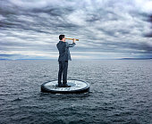 A businessman stands on a large compass as he looks through a spyglass while navigating through a sea that is beginning to turn rough.