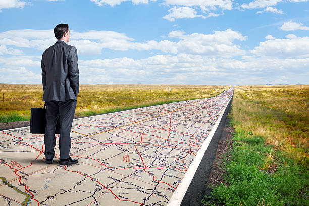 businessman stands on long road with road map painted on it - road map stock photos and pictures