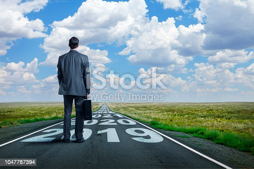 A businessman stands on and looks down a long, straight, rural road that has