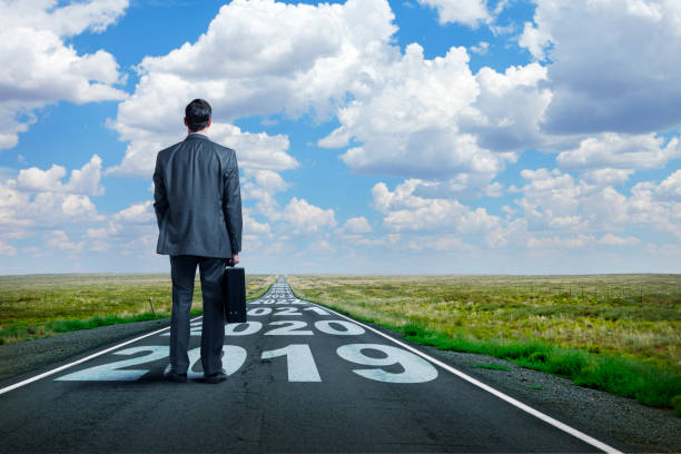 Businessman Stands On Long Road With Series Of Years Painted On It stock photo