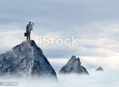 A businessman places his hand to his brow as he stands on a mountain top looking into the distance at two other mountain tops that rise above the clouds in the distance. An overcast sky provides ample room for copy or text.