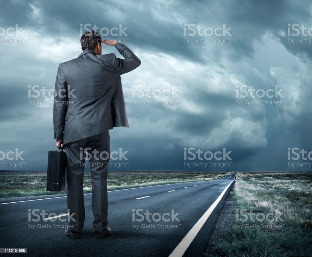 Businessman Stands On Road Looking Toward Storm On The Horizon stock photo
