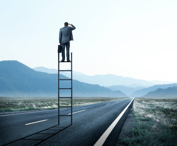 Businessman Stands On Tall Ladder On Long Road Looking Toward Mountains In The Distance stock photo
