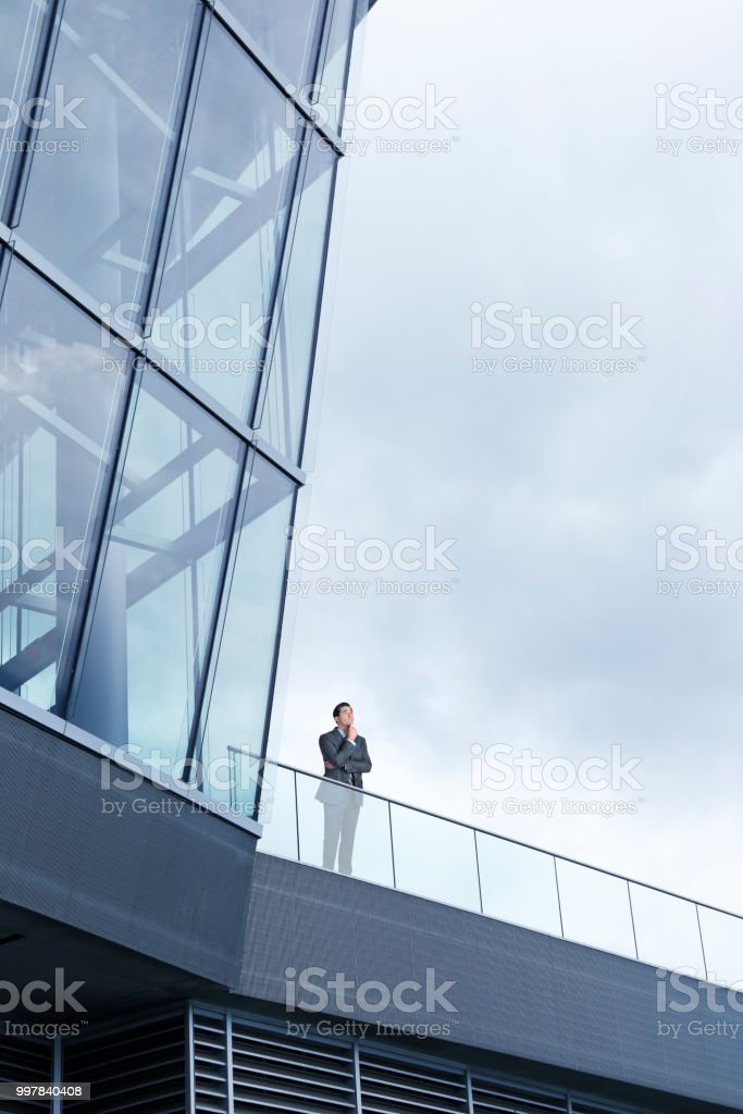 Businessman Stands Outside Modern Office Building stock photo