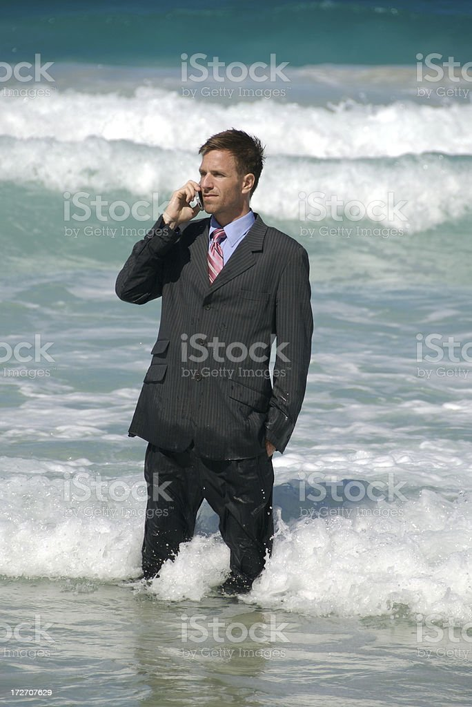 Businessman Stands Talking on Mobile Phone in Big Surf stock photo