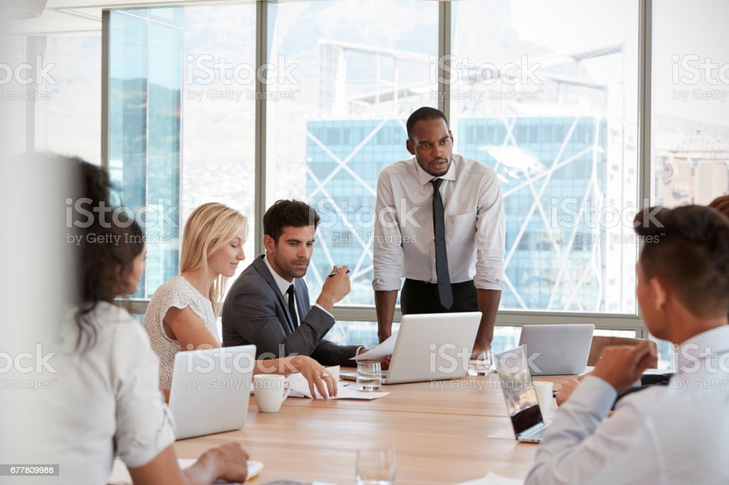 Businessman Stands To Address Meeting Around Board Table royalty-free stock photo