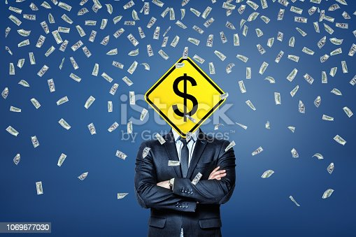 istock A businessman stands under a rainfall of dollar banknotes with a dollar road sign instead of his head. 1069677030