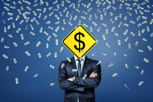 一個商人站在一張美元鈔票的雨下, 上面有一個美元的路標, 而不是他的頭。 - 被砍頭 個照片及圖片檔