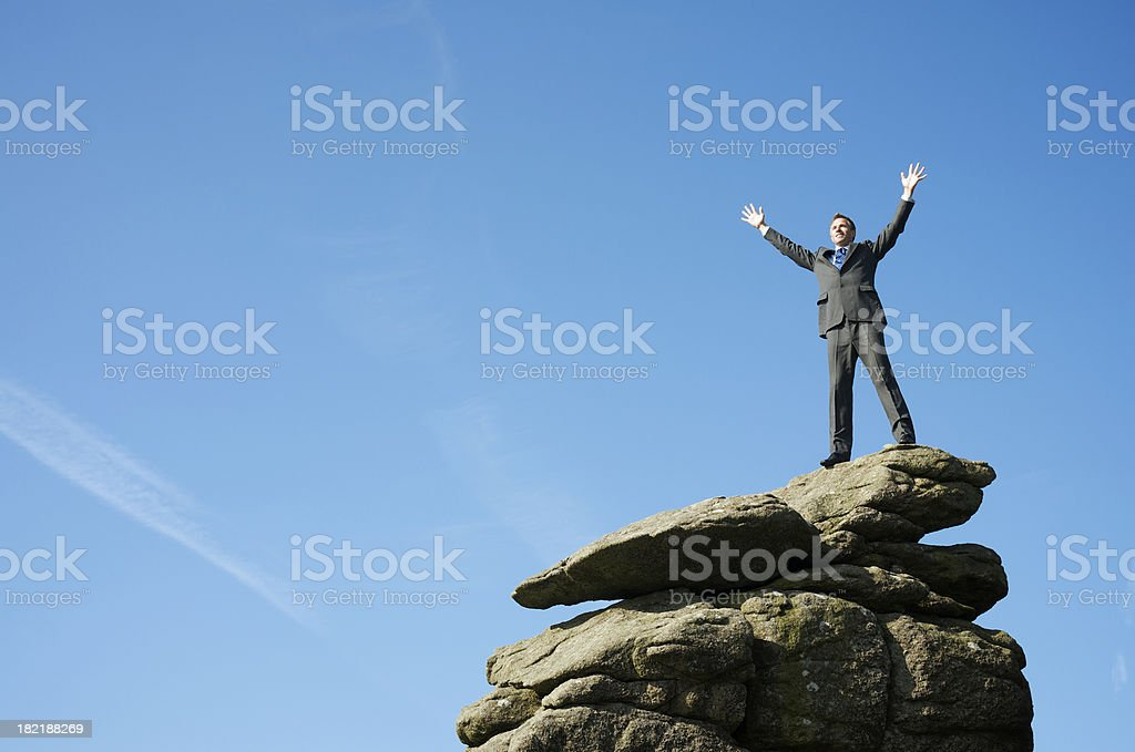 Businessman Stands Victorious on Rock royalty-free stock photo