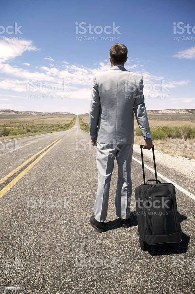 Businessman Stands w Suitcase on Roadside royalty-free stock photo