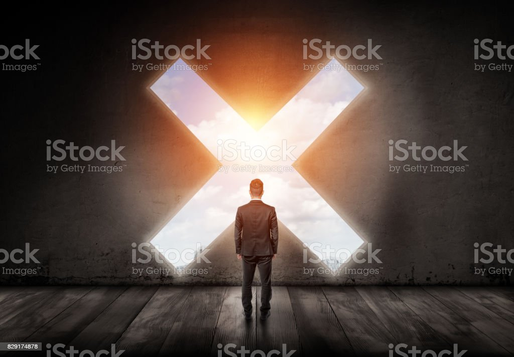 A businessman stands with his turned back and looks into a cross-shaped hole in a concrete wall stock photo