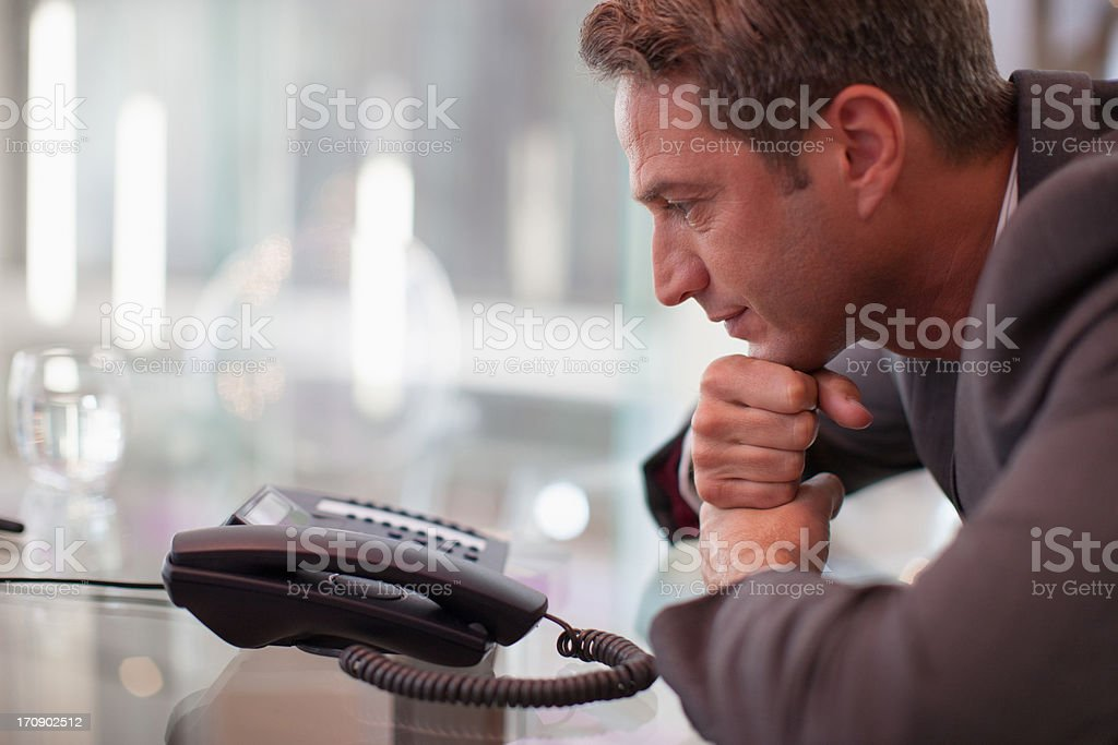 Businessman staring at telephone waiting for it to ring stock photo