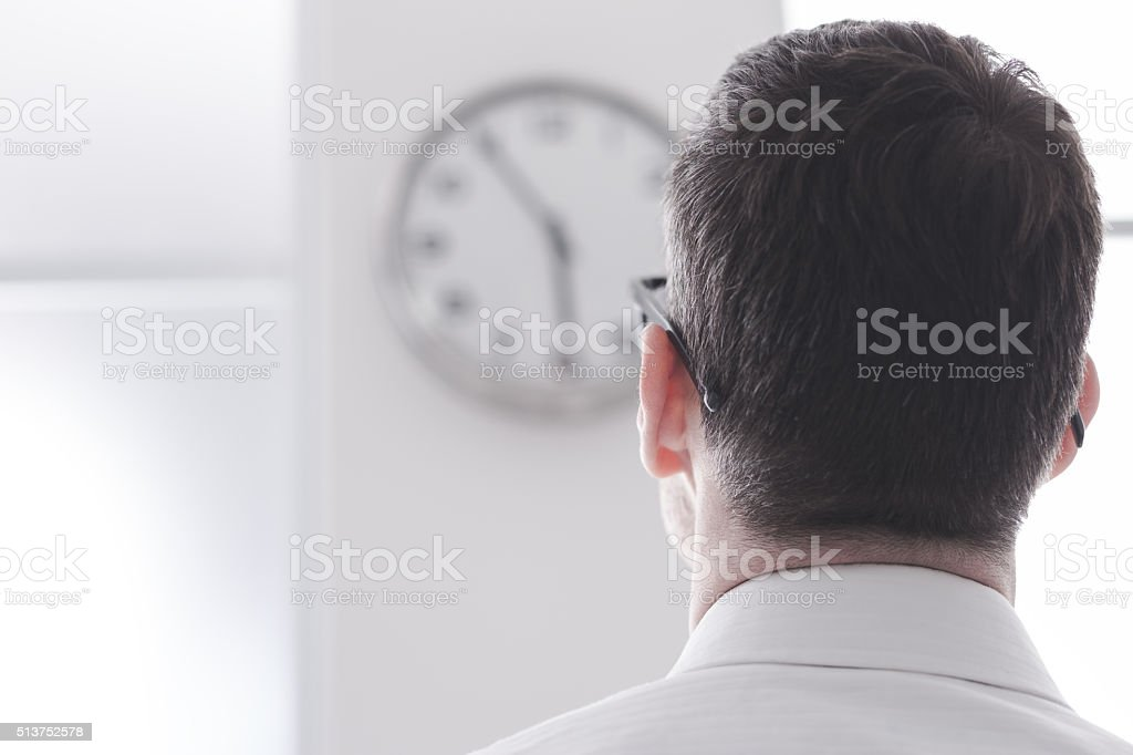 Businessman staring at the clock stock photo
